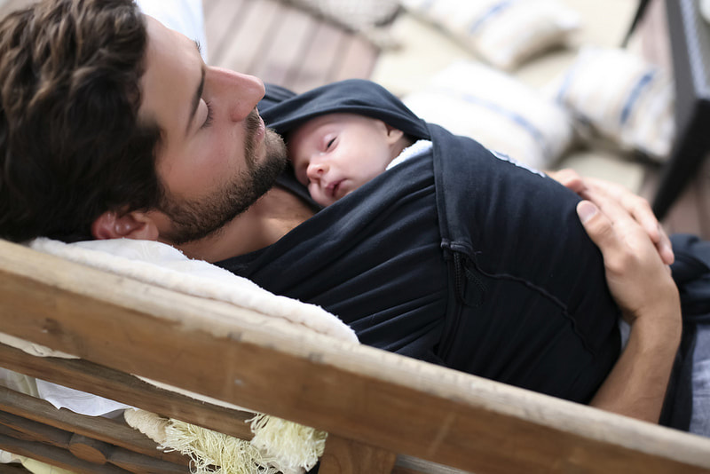 Relax your muscles and your mind with babywearing. More about why babywearing is good for you at adjoyn.com/news. [Image of a white bearded man reclining and wearing a baby on his chest in a black stretchy wrap.]