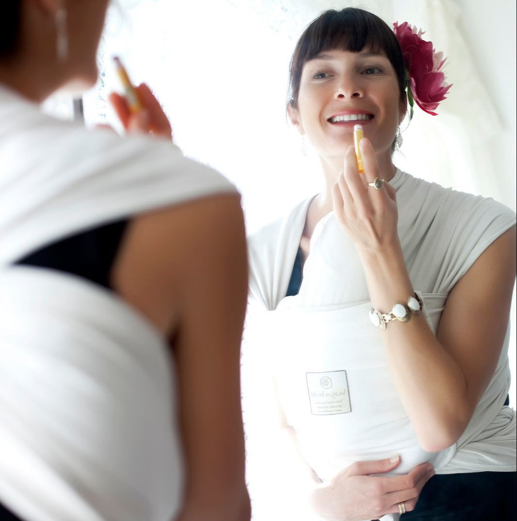 Babywearing not only helps you look stylish, it helps you FEEL put together too. More reasons why YOU should be babywearing at adjoyn.com/news. [Image of a woman with tan skin looking in a mirror and applying lipstick while wearing a baby on her chest in a white stretchy wrap.]
