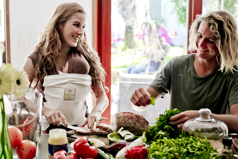 Babywearing allows for preparation - and consumption! - of foods to nourish you so you can care for your baby - more reasons why babywearing is for you at adjoyn.com/news [Image is a stock photo of a white man and woman preparing food together. The woman is wearing a young baby in a stretchy wrap.]