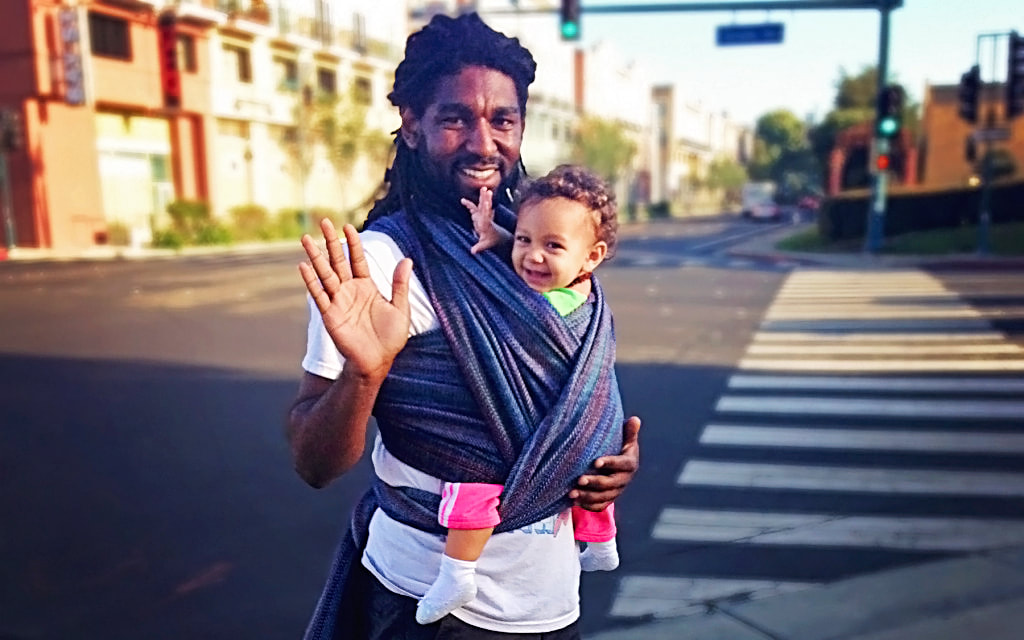 That baby is getting SO SMART. Babywearing helps make babies smarter, and it has a whole bunch of benefits for the wearer, too. More at adjoyn.com/news [Image of a man with dark skin wearing a toddler on his front in a woven wrap. He's standing near a street and waving; both the adult and toddler are smiling at the camera.]