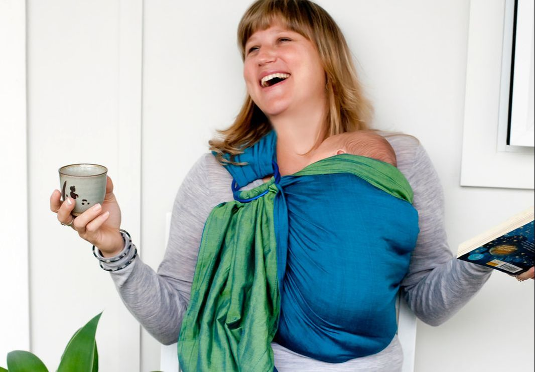 A very happy wearer, a very satisfied wearee - more on why babywearing can help you at adjoyn.com/news. [Image of a white woman laughing while wearing a baby on her front in a blue and green ring sling. She's holding a clay mug with one hand and a book with the other.]